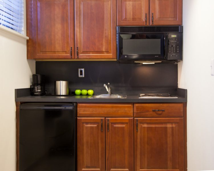 kitchen in hotel guest room with fridge and microwave