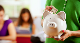 woman placing money into a piggy bank