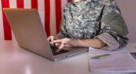 woman in military clothing on her computer