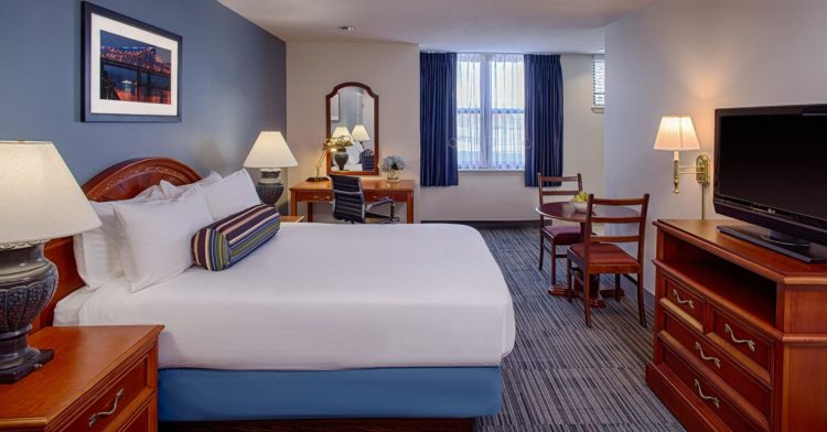 king bed hotel room with workstation and dining table
